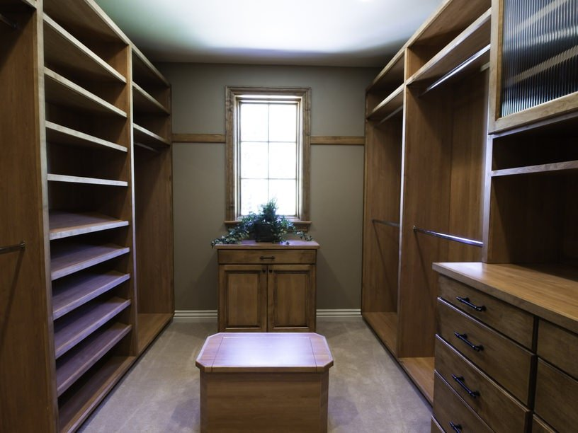 Natural wood storage matches the island and cabinet by the wooden framed window inviting natural light in. It has carpet flooring and a gray wall that's lined with white molding.