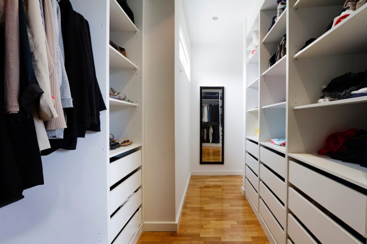 Minimalist walk-in closet boasts rich hardwood flooring and white cabinets that blend in with the walls contrasted by a black framed mirror.