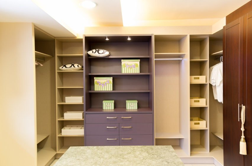 The warm walk-in closet features a granite top island and wooden cabinets that stand out against the beige shelving and luminous ceiling.