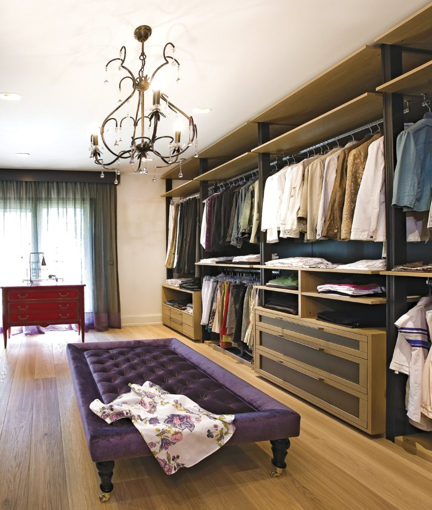 This walk-in closet is furnished with a red dresser and a large purple tufted seat over the hardwood flooring. It is illuminated by a fabulous ornate chandelier and recessed ceiling lights.