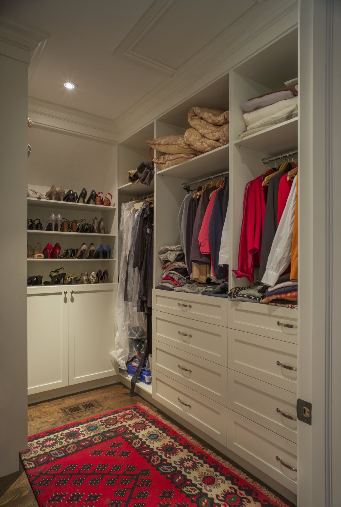 A red printed rug adds a nice accent in this walk-in closet with hardwood flooring and white cabinets blending in with the walls and ceiling that's lined with crown molding.