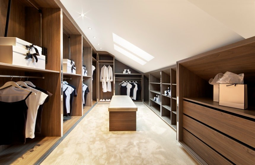 Unisex walk-in closet with beige carpet flooring and a shed ceiling fitted with recessed lights and skylights. There's a cushioned bench in the middle surrounded by wooden modular cabinets.