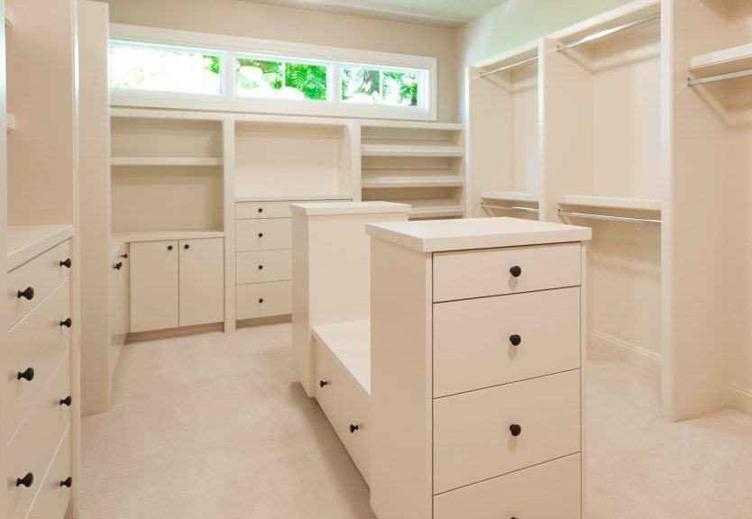 This walk-in closet sports a cohesive look showcasing white cabinets and a matching island over carpet flooring. It includes glazed windows that bring natural light in.