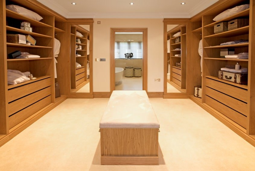 Symmetrical walk-in closet with a cushioned seat and wooden storage along with full height mirrors that create a larger visual space in the area. There's a doorway in the middle that opens to the primary bathroom.