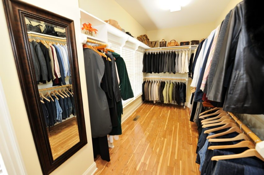 Galley style walk-in closet boasts a pole system wardrobe against the light yellow walls. It has hardwood flooring and a rectangular mirror on the side adding a dark contrast to the area.