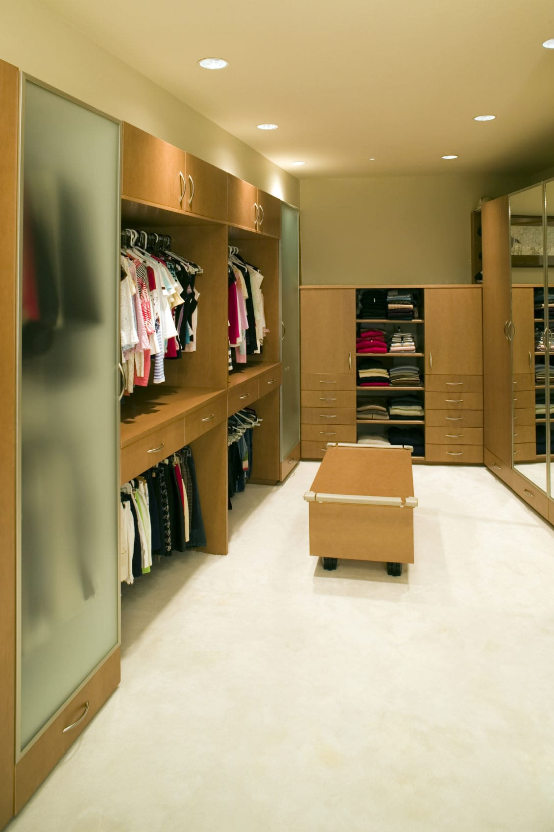 Wooden cabinets with mirrored and frosted glass doors surround a mobile seat over the beige carpet flooring. It is illuminated by recessed lights that are fitted on the regular ceiling.