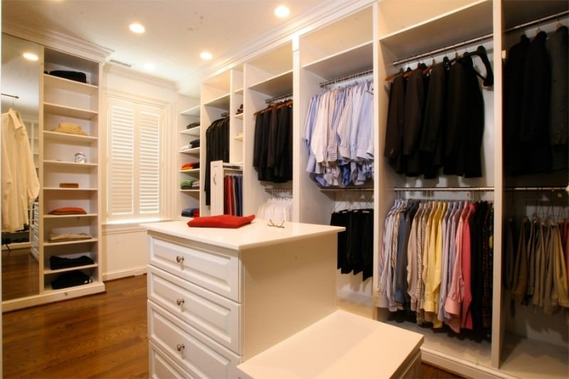 White window shutters and modular cabinets surround a quartz top island with a built-in seat on the side. This walk-in closet has rich hardwood flooring and a regular ceiling fitted with recessed lights.
