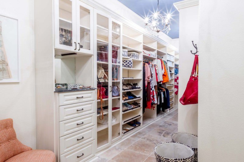 Narrow walk-in closet illuminated by a crystal beaded chandelier that hung from the blue tray ceiling. It showcases ample storage and a coral tufted chair with a white framed artwork on top.