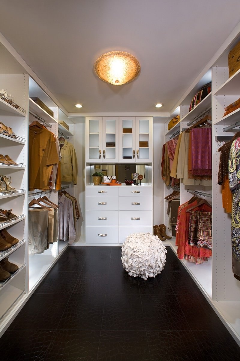 A stylish round seat over black tiled flooring is the highlight in this walk-in closet with open storage and white cabinets illuminated by an amber flush mount light along with recessed ceiling lights.