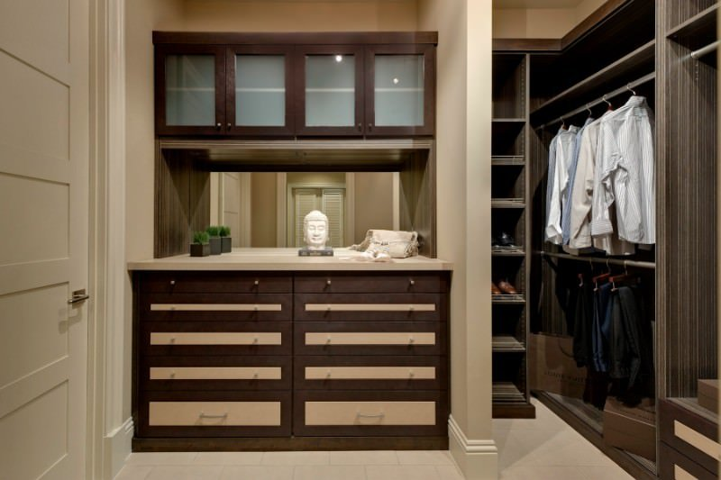 The unisex walk-in closet offers wardrobe rods and single column cubbies along with brown cabinets that are fitted with a mirrored backsplash. It is decorated with small faux plants and a Buddha head sculpture.