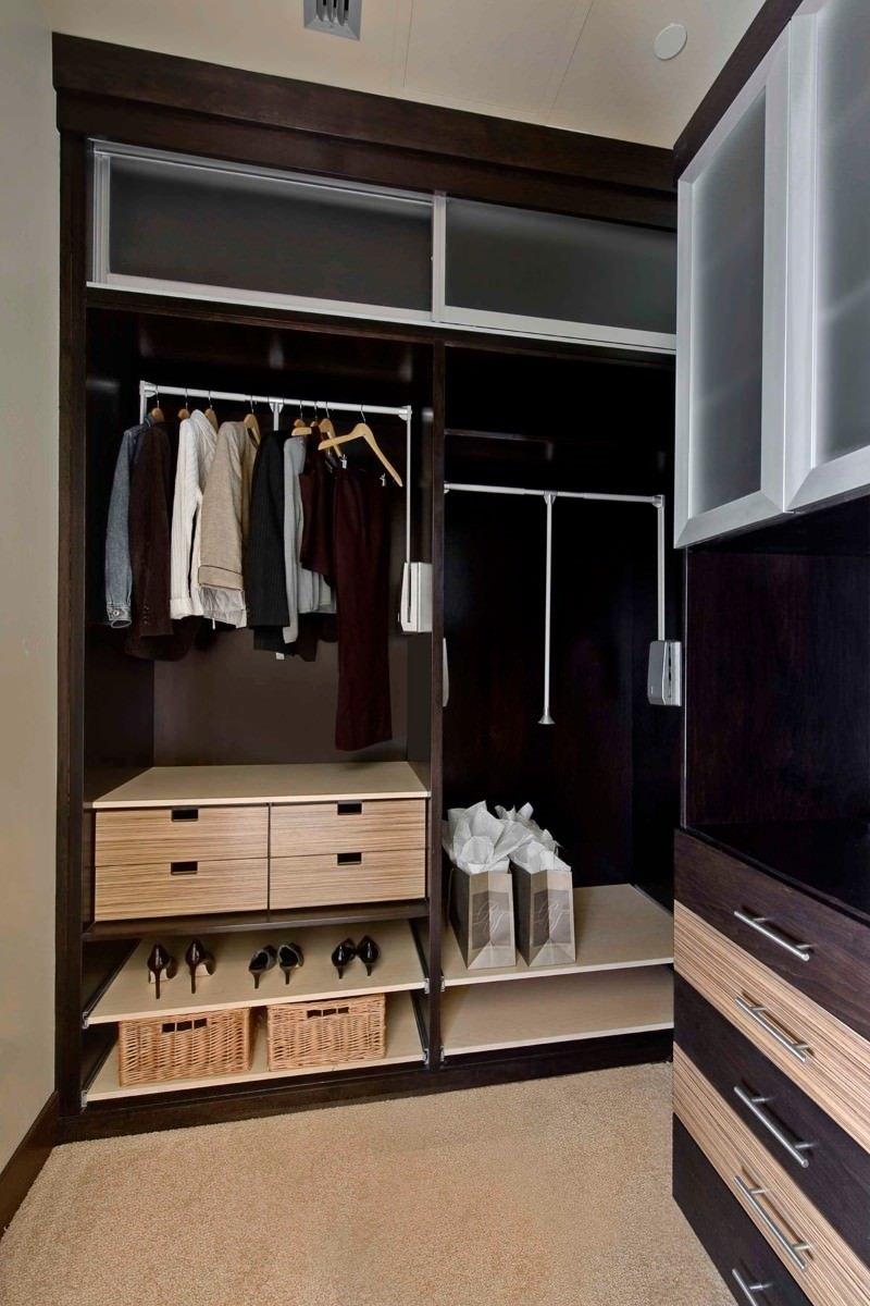 Two-tone modular cabinets add an exciting touch in this walk-in closet with beige carpet flooring and taupe walls matching with the regular ceiling.