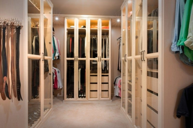 This walk-in closet features wardrobe rods and glass front cabinets illuminated by recessed lights. It blends in with the beige walls and carpet flooring achieving a unified design.