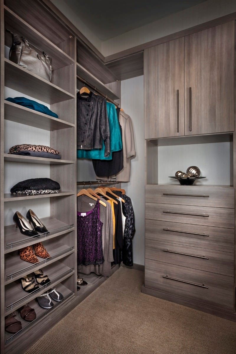 A closeup look at this walk-in closet with natural wood dresser over striped flooring along with open shelving for storing shoes and bags.