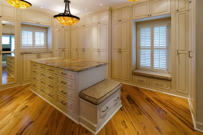 Cozy walk-in closet with white wardrobe cabinets and a built-in window seat nook topped with an animal print cushion. It includes a granite top island with a built-in seat on the side lighted by amber dome pendants.