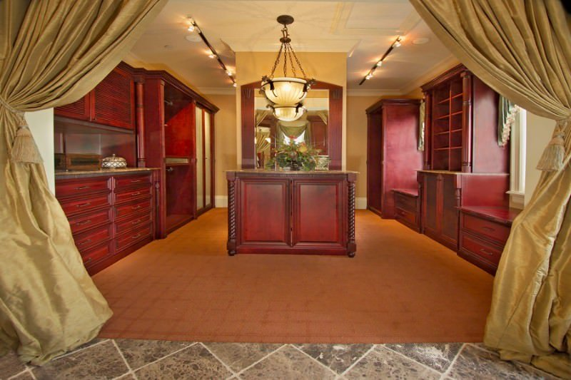 A view of the walk-in closet through the gold draperies offering redwood cabinets and a matching island situated across the wall mirror. It is illuminated by a glass dome pendant and black track lights.