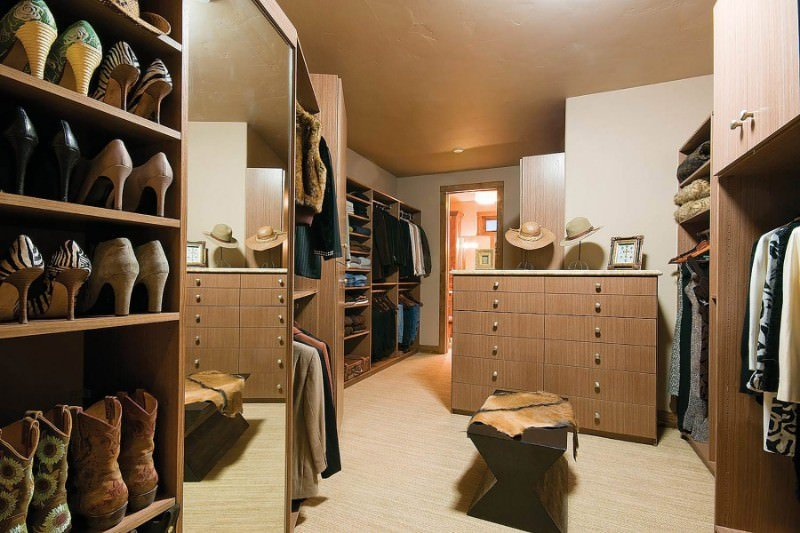 Unisex walk-in closet with open storage and a wooden counter fitted with ample drawers. It is complemented by a brown bench that's topped with a cowhide throw.