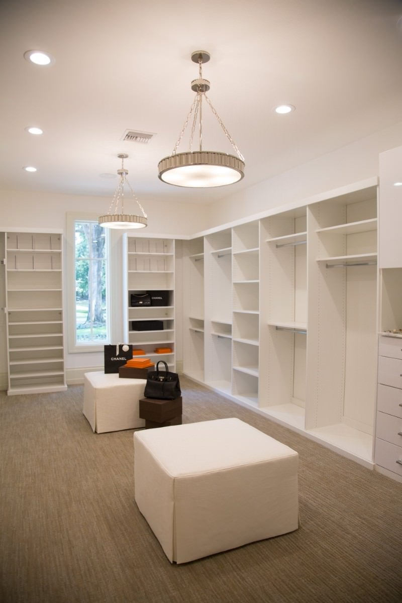 White walk-in closet boasts open shelving and a pair of skirted ottomans over the taupe carpet flooring. It is illuminated by round chandeliers and recessed ceiling lights.