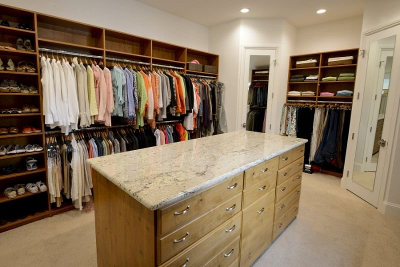 This walk-in closet features wooden storage and white doors fitted with full-length mirrors. There's a light wood island in the middle that's topped with a beige granite countertop.