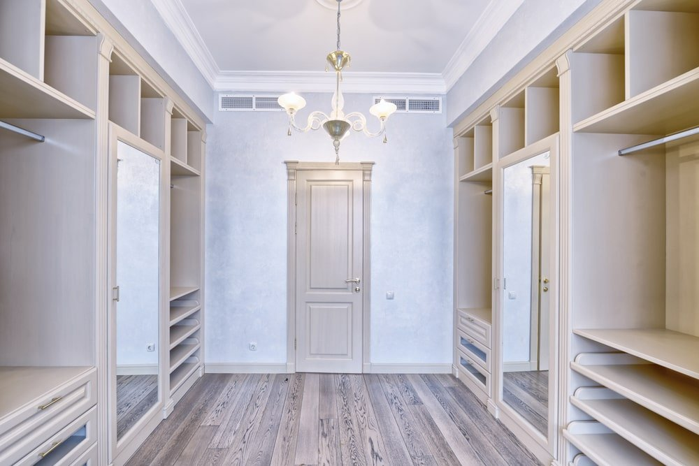 Light wood cabinets with mirrored doors add perfect symmetry in this walk-in closet with natural hardwood flooring and a lovely glass chandelier that hung from the regular white ceiling.