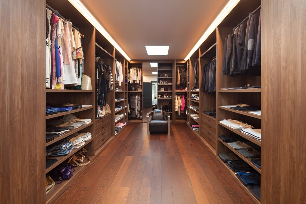 This walk-in closet features a sleek leather chair underneath the skylight along with dark wood modular cabinets that blend in with the wide plank flooring. It is illuminated by stripped lights fixed on the regular white ceiling.
