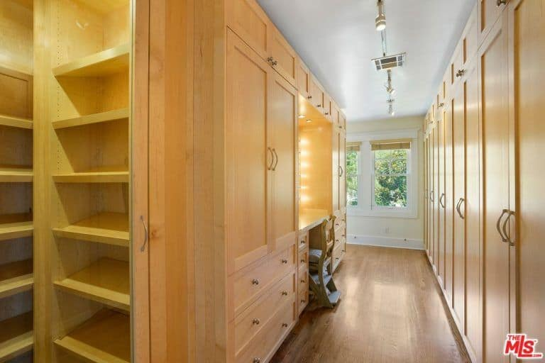This walk-in closet showcases light wood wardrobes and shelving along with a built-in vanity that's paired with a cushioned chair. It includes track lights and white framed windows covered in wicker roller blinds.