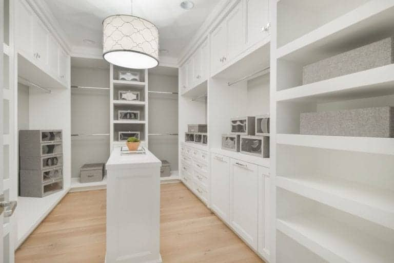 White cabinets and shelving match the center island that's lighted by a patterned drum chandelier. It goes well with the light hardwood flooring breaking a monotonous scheme.