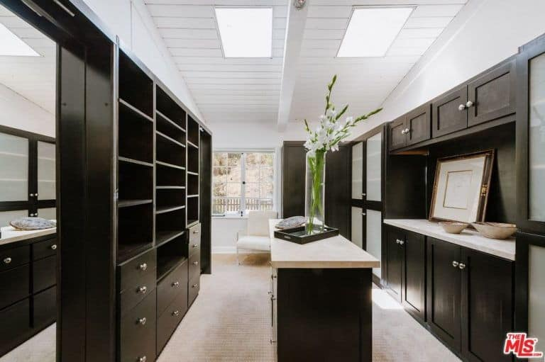 Black cabinets along with a matching island and counters run throughout this walk-in closet with beige carpet flooring and a shiplap ceiling fitted with skylights.
