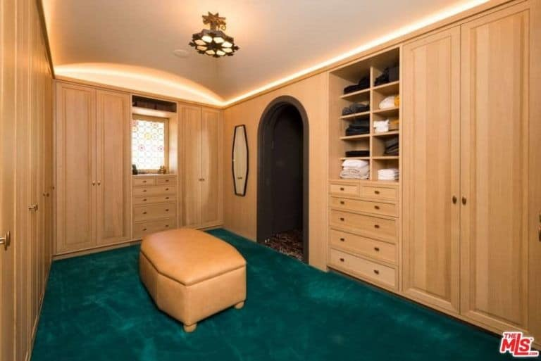 Green carpet flooring provides a sleek contrast to the light wood cabinets and a matching beige leather ottoman. This walk-in closet offers an arched doorway and a barrel vaulted ceiling mounted with a lovely semi-flush light.