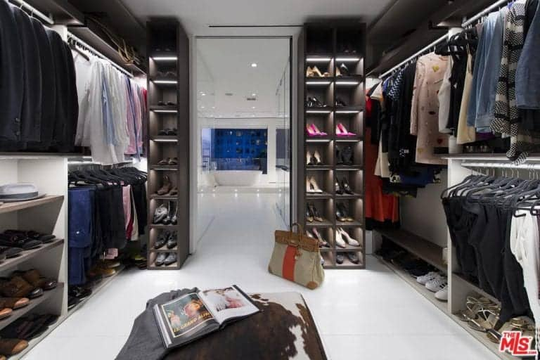 A custom cowhide ottoman complements the open storage and shoe cubbies over white tiled flooring. There's a view of the freestanding tub from the open doorway of this walk-in closet.