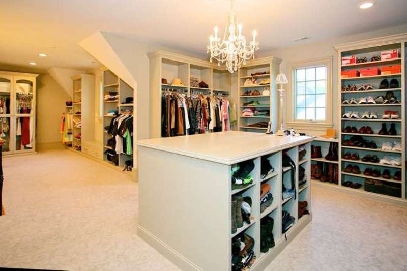 A fancy crystal beaded chandelier illuminates this walk-in closet boasting ample storage in taupe along with a matching island that's fitted with built-in cubbies. There's a white framed window on the side that allows natural light in.