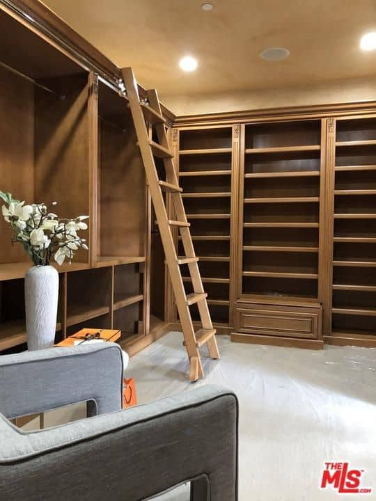 Unisex walk-in closet with wooden storage and a matching ladder accompanied by an upholstered gray armchair over white flooring. It is illuminated by recessed lights that are fitted on the regular beige ceiling.