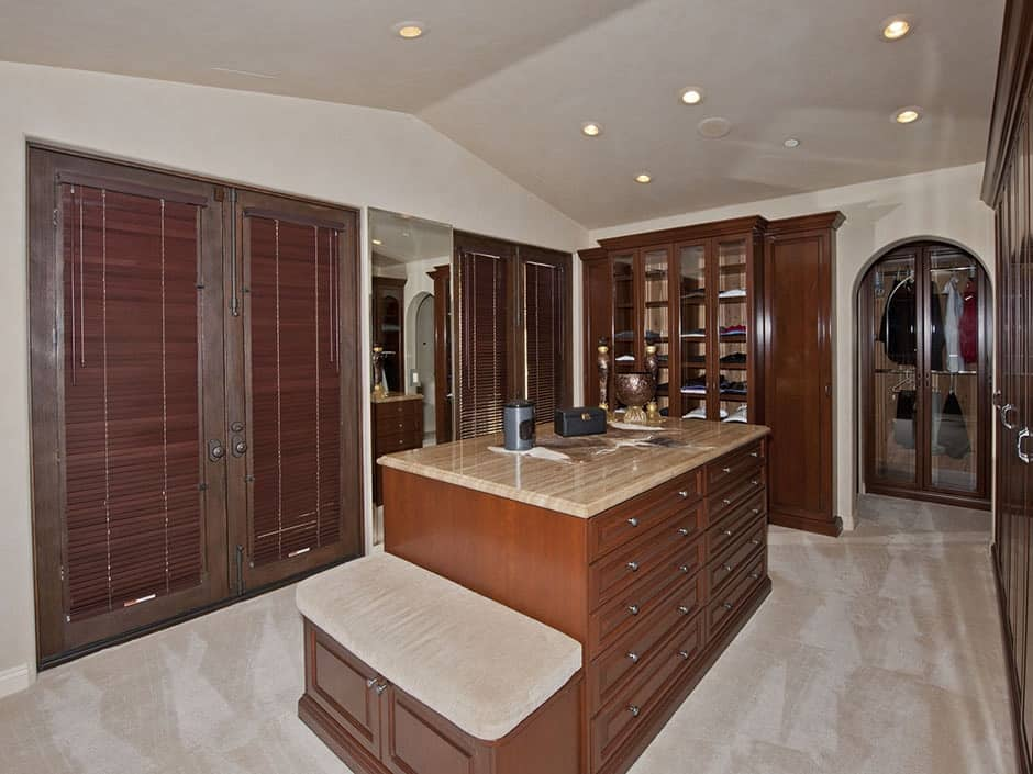The beige walk-in closet features wooden and glass front cabinets along with French doors that are covered in brown roller blinds. There's a granite top island in the middle that's integrated with a built-in seat on the side.