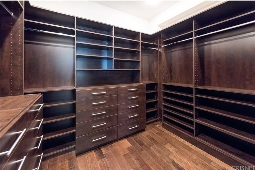A simple walk-in closet filled with open shelving and dark wood drawers that are fitted with stainless steel pulls. It is contrasted by white walls and a matching regular ceiling.