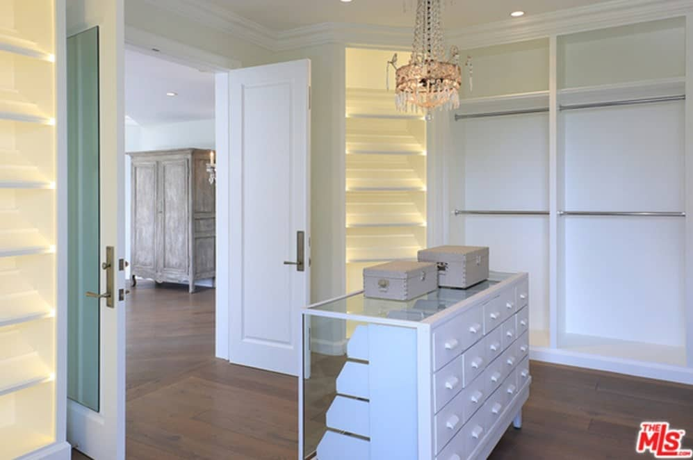 A white double door opens to this walk-in closet with open storage and a glass enclosed island fitted with white drawers. It is illuminated by a gorgeous crystal chandelier and recessed ceiling lights.