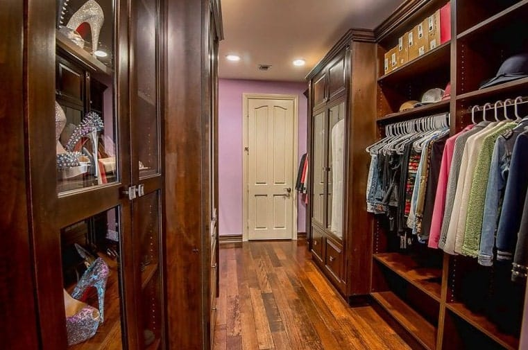 This walk-in closet offers a white door against the purple walls along with modular and glass front cabinets that blend in with the rich hardwood flooring.
