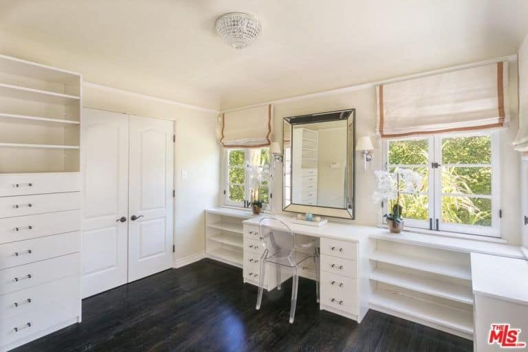 A glass round back chair sits at a built-in vanity that blends in with the open shelving and drawers. It is paired with a chrome framed mirror that's flanked by glazed windows covered in beige bordered roman shades.