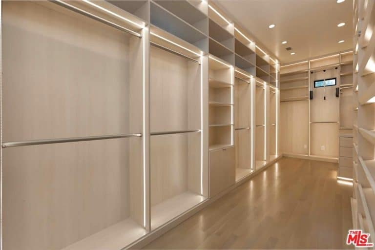 Recessed ceiling lights along with strip lights illuminate this large walk-in closet featuring full height storage that blends in with the light hardwood flooring.