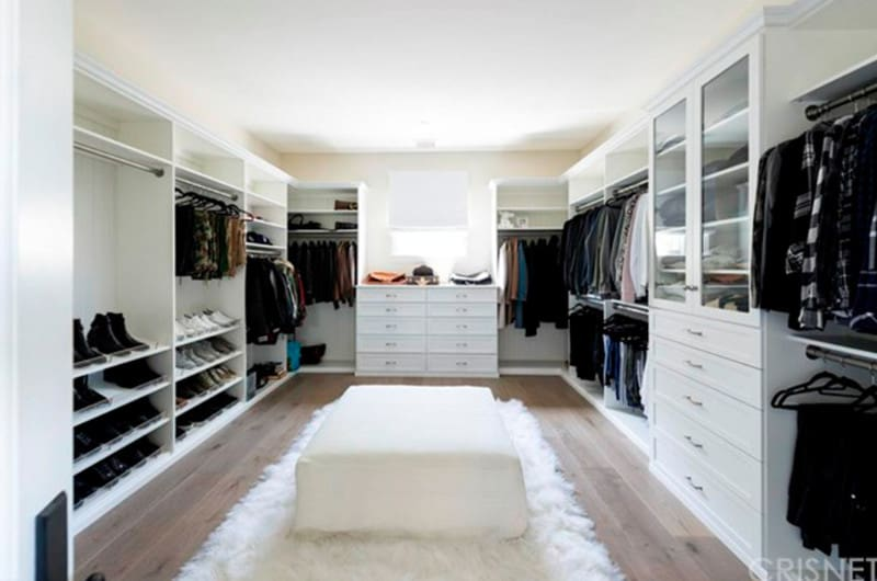 White drawers and open shelving surround the upholstered ottoman that sits on a faux fur rug over the natural hardwood flooring. It is accompanied by a picture window that's covered in a blackout roman shade.