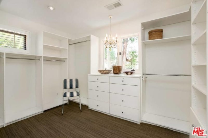 A stripe cushioned chair stands out in this bright walk-in closet with white shelving and drawers contrasted by the dark hardwood flooring. It is illuminated by a lovely candle chandelier along with natural light from the glazed windows.