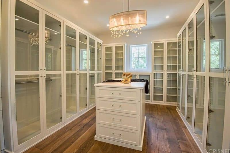 A fabulous chandelier illuminates the white island that sits on wide plank flooring. It is surrounded by glass front cabinets and a white framed window that invites natural light in.