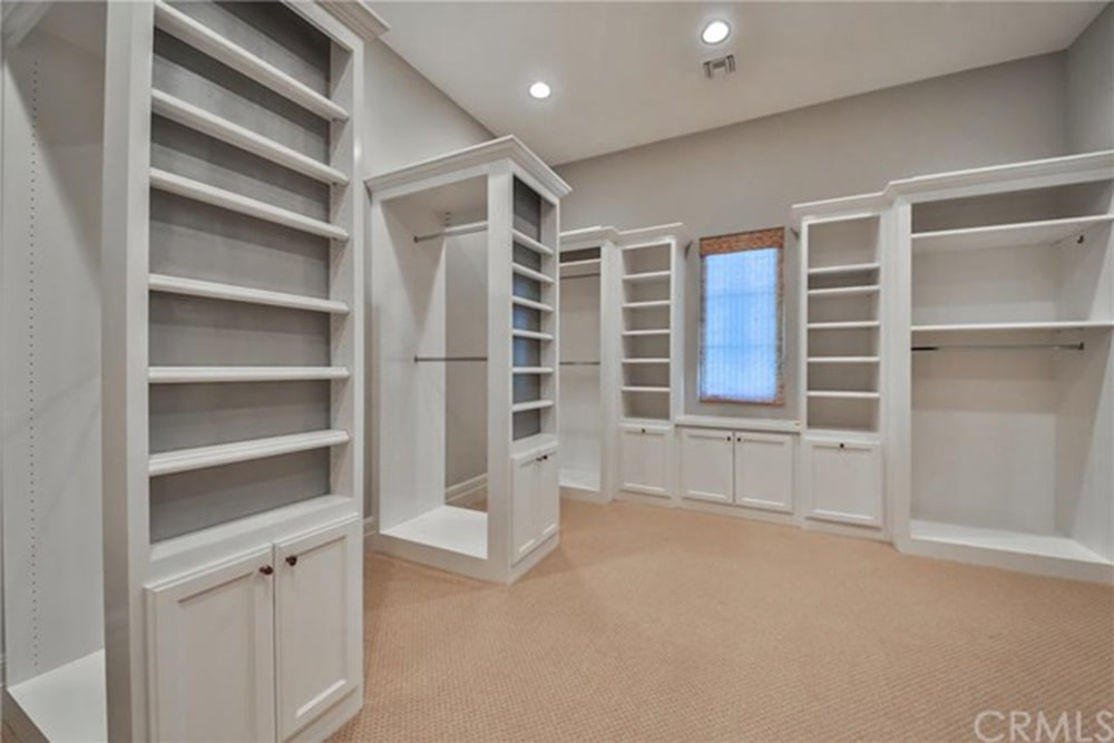 Spacious walk-in closet boasts white cabinets that harmoniously blend well with the walls lighted by recessed ceiling lights. It has beige carpet flooring and a glazed window covered in a translucent roman shade.