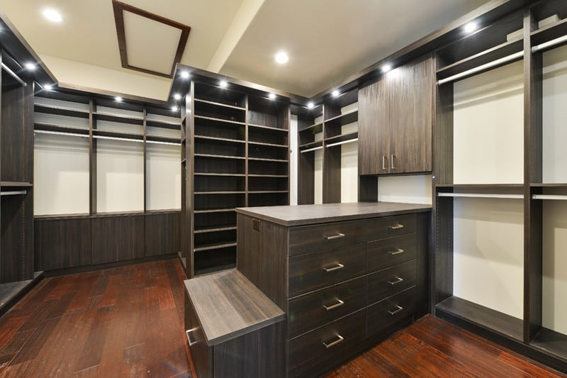 Unisex walk-in closet with hardwood flooring and recessed lights illuminating the dark wood wardrobes along with a matching counter that's integrated with a built-in seat on the side.