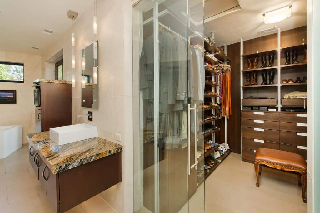 A walk-in closet situated inside the primary bathroom offering open shelving and dark wood drawers complemented by a leather cushioned stool that's lighted by a glass flush mount light.