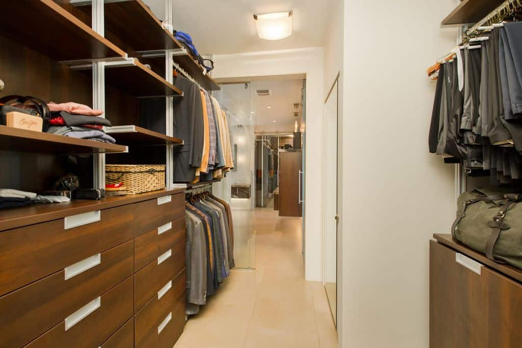 A glass flush light mounted on the regular white ceiling illuminates this walk-in closet showcasing glazed doors and dark wood storage over beige tiled flooring.