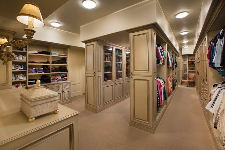 A large walk-in closet boasts a beige counter and ample storage complemented by a brown cushioned chair over carpet flooring. It is illuminated by vintage sconces and recessed ceiling lights.