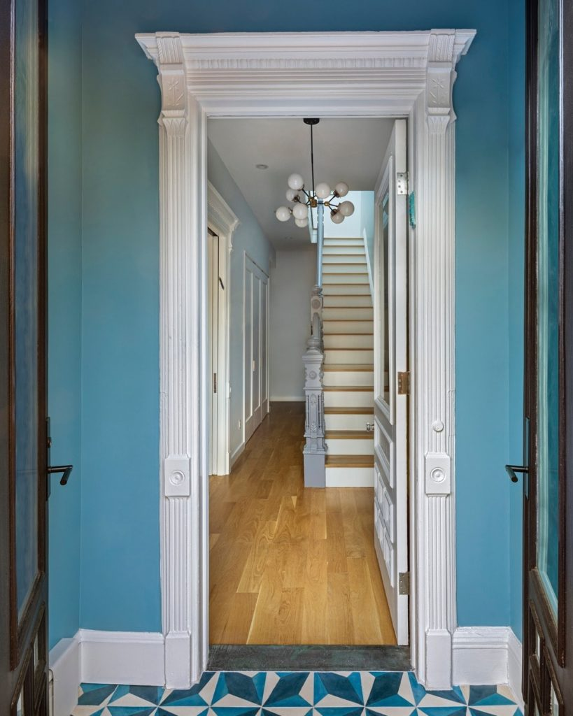 This simple Victorian-style foyer transitions from blue patterned floor tiles to hardwood as it moves into the secondary doorway that has an elegant white frame to the bottom landing of the wooden stairs that is topped with a modern decorative chandelier.