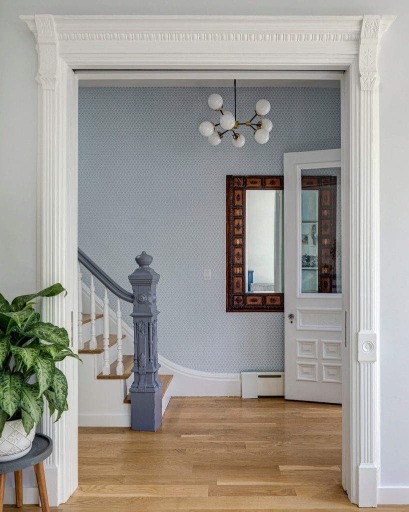 This is a different angle of the Victorian-style foyer where you can see that the bottom landing of the stairs is adorned with a wall-mounted mirror that has an elegant wooden frame that makes it stand out against the patterned light blue wallpaper.