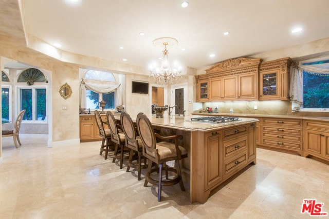 Well-lit kitchen features a fabulous crystal chandelier that hung over the granite top island complemented by beige round back chairs. It is surrounded by matching cabinetry and glazed windows that are dressed in sheer valances.