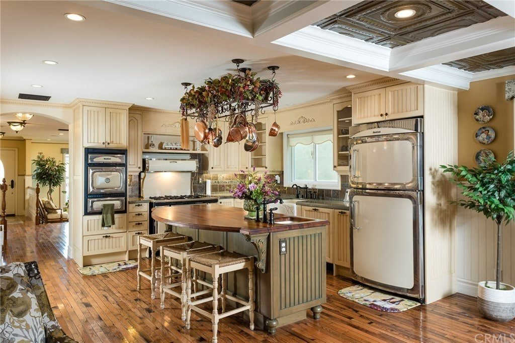 Victorian kitchen filled with white appliances and beadboard cabinetry along with a wooden top island that's lined with white counter chairs over the hardwood flooring. It includes a hanging pot rack wrapped in decorative plants.