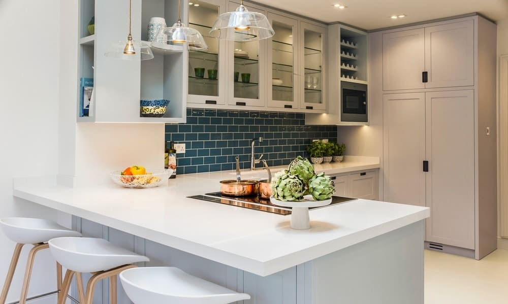 Blue subway tile backsplash adds a striking accent in this kitchen with gray and glass front cabinets flanked by open shelvings. It includes a quartz top peninsula with a built-in cooktop and sleek white stools illuminated by glass dome pendants.